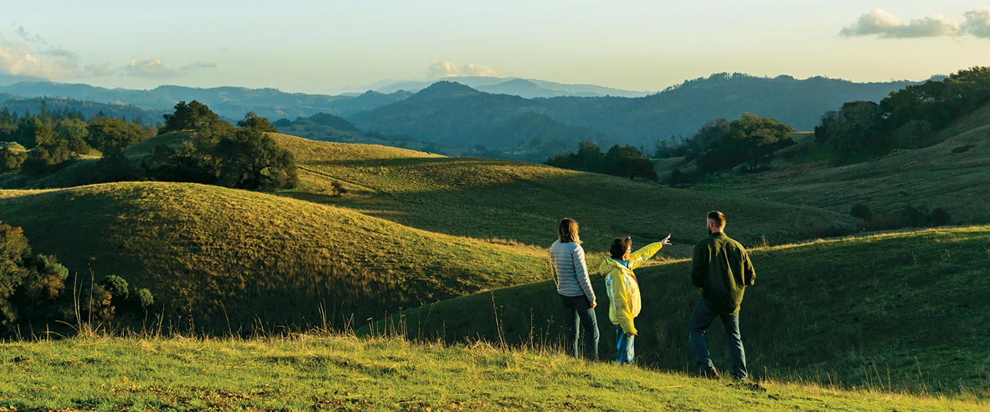 Grand vista of hill tops at sunset with 3 people in the foreground